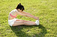 A young woman stretching her hands till her toes while exercising