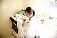 Young woman drinking cup of coffee in kitchen