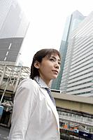 A low angle view of a woman with commercial buildings at the background