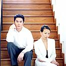 Businesswoman and a businessman sitting on a staircase