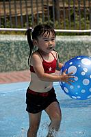 A girl in a pool with beach ball
