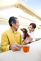 A Senior Adult Couple Having a Tea Break with a Dog in a Garden, Side View