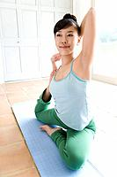 Young woman doing yoga exercise, stretching, front view