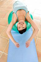 Young woman reclining on an exercise ball, stretching, high angle view (thumbnail)