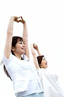 Two young women under the sky, stretching arms above head, low angle view