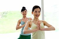 Young women doing yoga exercise, front view (thumbnail)