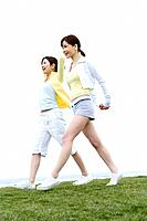 Young Women walking on lawn, low angle view