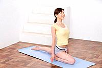 Young woman doing yoga exercise, stretching, high angle view