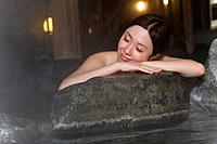 Woman in hot tub leaning on the rock, closing eyes, front view, Japan