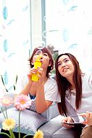 Two Young Adult Women Sitting on a Couch, One Blowing Soap Bubbles, Front View, Differential Focus
