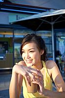 Young Lady Sitting at Outdoor Cafe, Holding Cold Drink, Looking Away