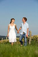 Germany, Bavaria, Young couple walking in meadow, holding hands,
