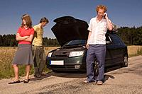 Germany, Bavaria, Three friends with broken down car