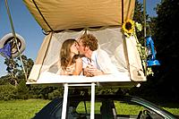 Germany, Bavaria, Young couple laying in tent