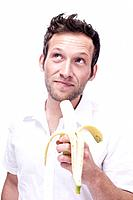 Portrait of a young man holding a banana, close_up