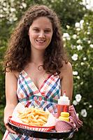 Woman holding tray of chips, ketchup and mustard