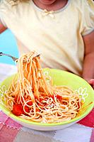 Small girl eating spaghetti with tomato sauce and Parmesan