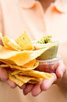 Woman holding plastic tubs of dips and nachos