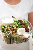 Woman holding plastic container of salad with feta & dressing