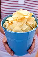 Woman holding crisps in blue bucket