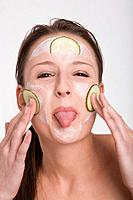Young woman applying a cucumber face mask, sticking her tongue out