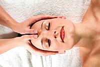 Young woman receiving facial massage, eyes closed, elevated view