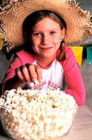 a blond girl eating popcorn