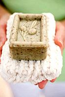 Woman holding olive soap on towel
