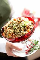 Woman holding bowl of vegetable rice with pecans Christmas