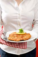 Woman holding plate of Wiener Schnitzel veal escalope