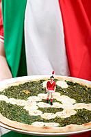 Football fan holding spinach and mozzarella pizza Italy