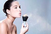 Young woman holding makeup brush, blowing, portrait