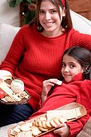 Mother and daughter on sofa with cheeseboard and crackers
