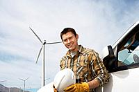 Engineer by car at wind farm portrait