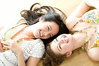 Two young women smiling and lying on floor, portrait for one