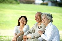 Young Woman with senior couple smiling and sitting on lawn, differential focus
