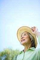 Senior woman in hat smiling and looking up at the sky, copy space