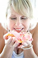 Senior woman holding and smelling flower petals, closing eyes