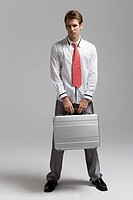 Businessman holding briefcase, portrait