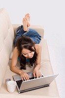 Young woman sleeping on sofa using laptop, elevated view