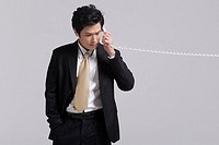 Young businessman holding telephone receiver