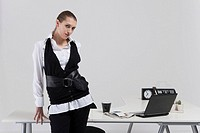 Portrait of young businesswoman standing by table in office