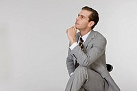 Businessperson sitting on chair, looking away