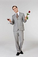 Businessman holding wine glass and rose, portrait