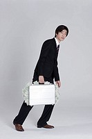 Young businessman holding briefcase full of money, walking