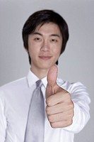 Young businessman with thumbs up, smiling