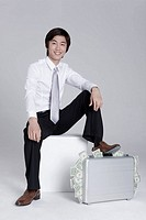 Young businessman sitting on block with feet on briefcase, portrait