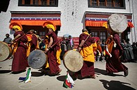 Nuns / monks in traditional dress with yellow orange hats and robes at 800 year old birthday celebration / rituals of the Buddhist Drukpa Lineage, Nar...