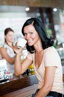 young woman in cafeteria drinks coffee