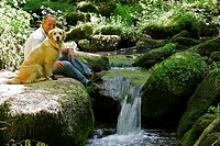 Man with Golden Retriever resting at stream, Monbach valley, Bad Liebenzell, Baden_Wurttemberg, Germany